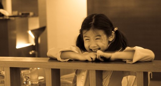 young girl standing at rail laughing