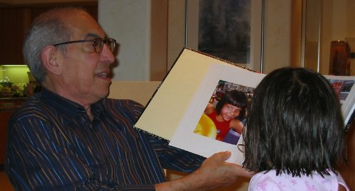Older man viewing a photo book with a child