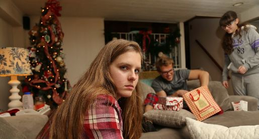 teenage girl scowling while siblings open presents